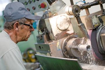metalworking industry: manufacture man operator working at horizontal rotary grinding machine