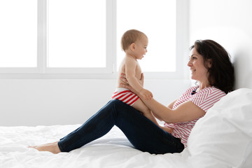 Mother sitting on bed smiling at baby on her lap