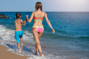 Mom and son are running along the sea shore. They are holding hands and moving away from the camera.