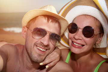 Joyful man and woman are making selfie photo on the beach against the sea.