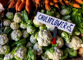 Cauliflower and carrots for sale at a farmers market.