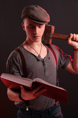 A young stylish guy with a big hammer reading big boock