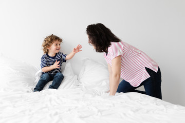 Mother and son playing on bed together