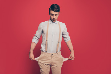 Professional, cunning magician, illusionist, gambler in casual outfit, showing two empty pockets out, standing over red background, looking down