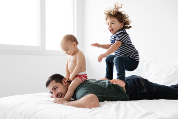 Dad lying on bed while son bounces on his back and baby straddles his neck