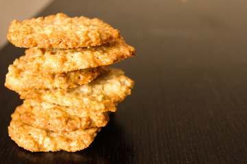 Pile of glossy brown homemade oatmeal cookies on dark wood table background. Tower of peanut oatcakes, healthy sweet home-baked products