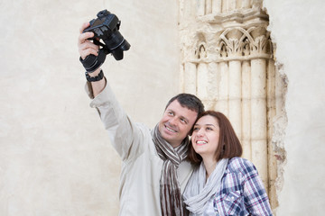 Traveling couple taking selfie together against ancient building background