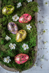 gold leaf on colorful Easter eggs with spring flowers on moss nest top view