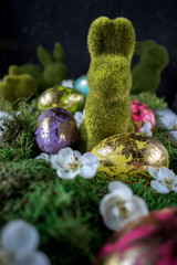 gold leaf on colorful Easter eggs with spring flowers on moss nest with topiary bunnies