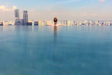 Woman Looking At Cityscape While Relaxing In Infinity Pool