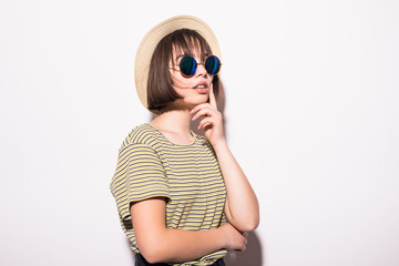 Young fashionable attractive hipster teen girl in sunglasses and straw hat isolated on white background .