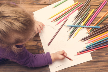 Little girl draws with pencils on a wooden table