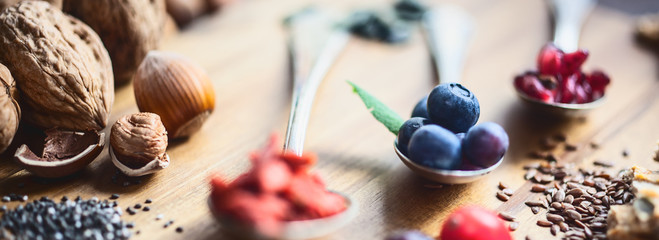 Superfood: Spoons of various superfoods on wooden background
