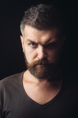 Bearded man. Hipster with serious face. Feeling and emotions. Man with long beard and mustache. Sexy bearded hipster with long beard and mustache has stylish hair on serious face.