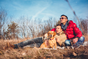 Gay male couple laying on blanket in grass with dog
