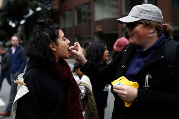 A demonstrator feeds a chained demonstrator during a rally to denounce raids to apprehend immigrants without legal status, according to organizers, outside the ICE office in San Francisco