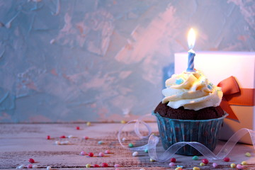 Cupcake with birthday candle and gift box. Top view.