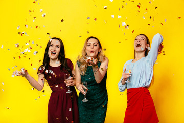 Happy March 8. Cheerful beautiful girls playing with confetti, blowing, having fun together while celebrating the women holiday, standing over yellow background. Dressed in colorful clothes.