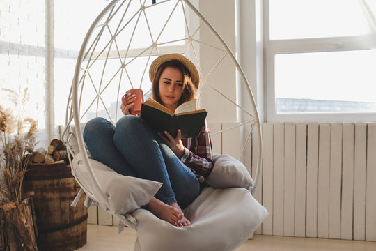 Girl relaxes reading a book and drinks tea.