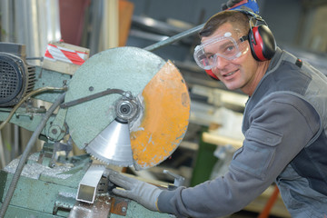Portrait of worker by industrial circular saw