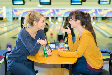 Ladies talking at table in bowling alley