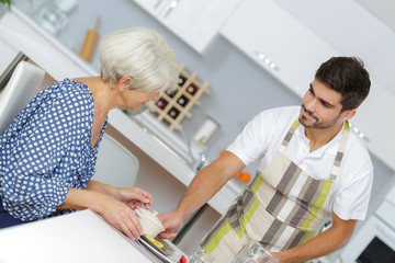 nurse serving breakfast to senior woman at home