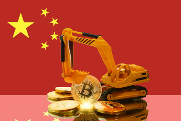 bitcoin mining concept; miniature Excavator and Bitcoin coins (physical version) against the background of the flag of China