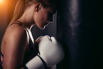 sexy fighter girl in gym with boxing bag. Long hair woman fitness model resting after boxing