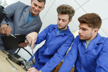 teenage apprentices fixing an object