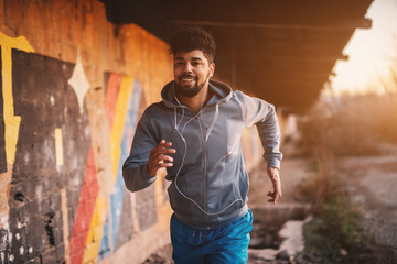 Portrait of active motivated afro-american young attractive athletic man with earphones running inside of the abandoned place.