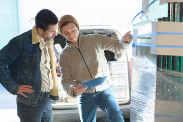 2 male workers checking stock in a warehouse