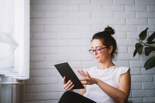 Middle aged attractive woman looking at tablet searching online.