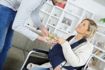 male caregiver helping old female on wheelchair