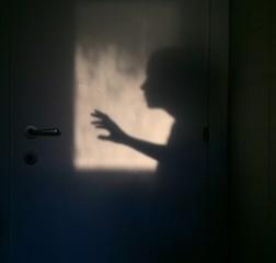 silhouette di una persona che apre la porta