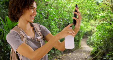 Pretty African woman using smartphone in Costa Rican jungle