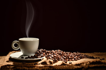 Poster de jardin Salle de cafe Cup of coffee with smoke and coffee beans on black background