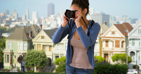 A Latina woman takes pictures of the Painted Ladies in San Francisco. A Hispanic millennial girl takes a photograph near downtown San Francisco
