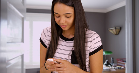 A young girl uses her smart phone at home. A teen uses her mobile phone to go on social media