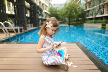 little kid girl take photo on table, tsitting close to blue swimming pool wearing flower and hold toy. concept of new technologies travel, recreation or holiday family time on sunny day