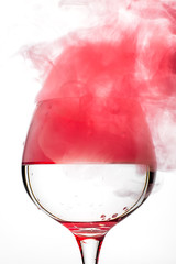 Wine glass with red smoke inside
