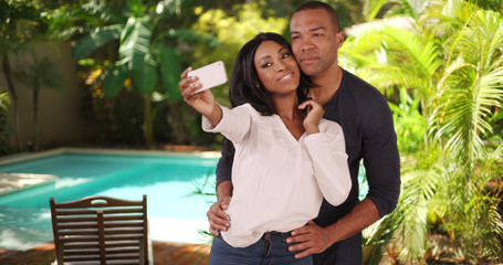 Black couple on vacation in Caribbean taking selfie together by a pool. African American couple at spa while travelling