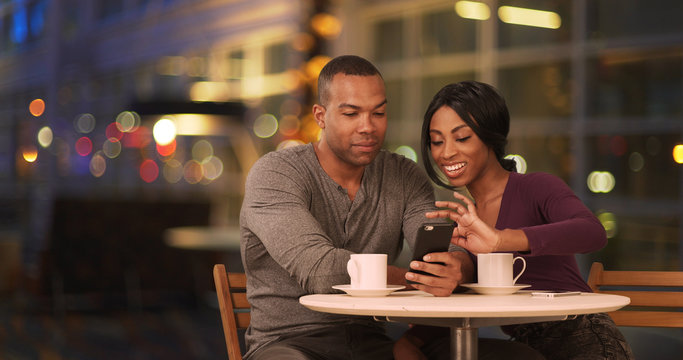 Happy Black couple using smart phone in coffee shop at night. African American man and woman using cellphone while drinking in cafe during evening. Millennials dating