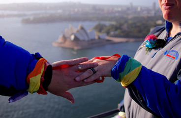 Warren Orlandi and Pauly Phillips display their rings after they became the first same-sex couple to marry atop of the Sydney Harbour Bridge, just two days out from the 40th anniversary of the Sydney Gay and Lesbian Mardi Gras