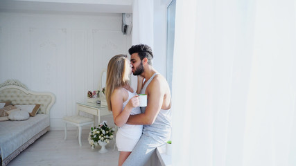 Delicate and Charming Young Lovers of Heart, Two Halves Are Opposite Each Other at Window, Hugging and Kissing, Guy Laugh Girl and Together They Drink Morning Green Tea in Bedroom With White Walls in
