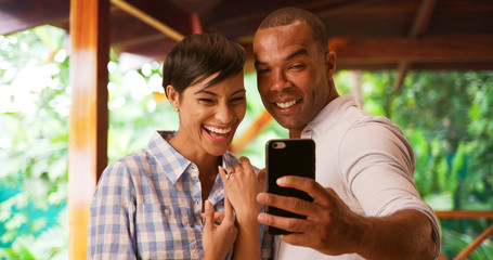 A black couple takes a selfie to celebrate their engagement. An African American man and woman take a picture using a smart phone of her new wedding ring