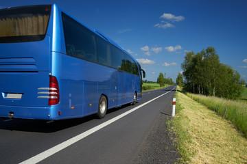 Blue bus traveling on asphalt road in a rural landscape