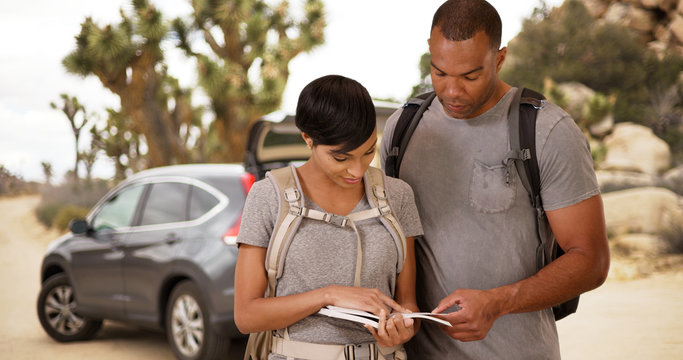 A black couple hiking look for directions. An African American man and woman read before going on a trip