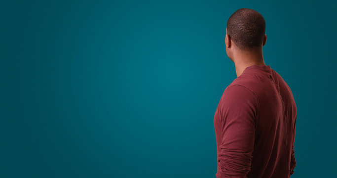 An African American man looks away from camera standing on a blue background. A black man with his back to camera poses on a blank backdrop