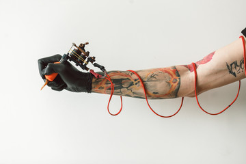 hand tattoo artist with the tattoo machine on a white background. the red wires