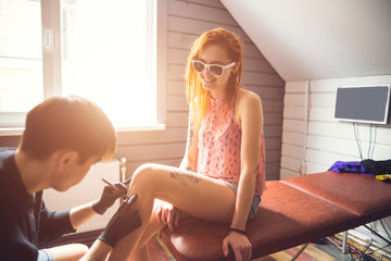 woman in sunglasses and red hair decided to get a tattoo. woman sitting on the couch. man makes a sketch of the pattern on the leg of the girl.